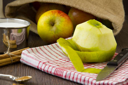 Ingredients set out for a traditional apple pie, with a partly peeled apple. Part of a series of images showing the preparation of traditional apple pie.