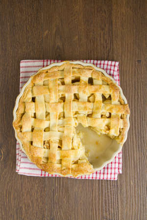 Freshly cooked apple pie with lattice pastry top on red gingham cloth, with a wedge removed. Part of a series of images showing the preparation of traditional apple pie. Stock Photo