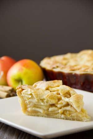 Slice of freshly made apple pie with pastry lattice top, on flat plate with apples, cinnamon sticks and the rest of the pie out of focus behind, with copy space. Part of a series of images showing the preparation of traditional apple pie. Stock Photo