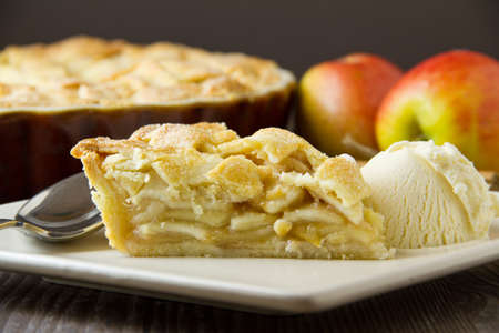 Slice of freshly made apple pie, a la mode, with pastry lattice top, on flat plate with apples, cinnamon sticks and the rest of the pie out of focus behind. A spoon and a scoop of vanilla ice cream sit on the plate. Part of a series of images showing the  Stock Photo