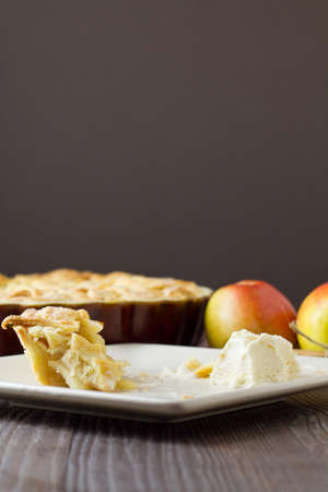 Slice of freshly made apple pie, a la mode, with pastry lattice top on flat plate with apples, cinnamon sticks and the rest of the pie out of focus behind. Half eaten pie with ice cream. Part of a series of images showing the preparation of traditional ap photo