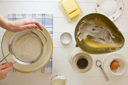 Ingredients for English scones laid out on white wood, with flour being sifted. Part of a series showing the preparation of scones. Stock Photo