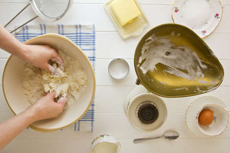 Ingredients for English scones laid out on white wood, with butter being rubbed into flour. Part of a series showing the preparation of scones. Stock Photo