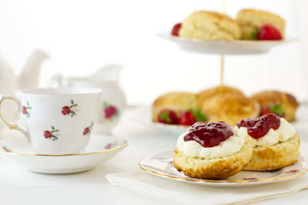English Cream tea scene with scones, Devonshire style, on china plate with teacup and saucer. Part of a series showing the preparation of scones. Stock Photo