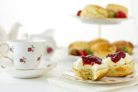 English Cream tea scene with scones, Devonshire style, with a bite taken out. Part of a series showing the preparation of scones. Stock Photo
