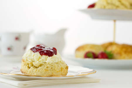 English Cream tea scene with scone offset, Devonshire style, on china plate with cake stand behind. Part of a series showing the preparation of scones. Stock Photo
