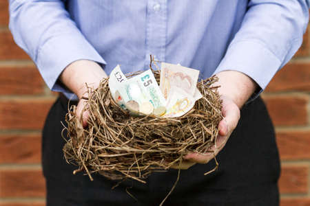coppers: Man holding nest filled with Btitish money. This nest was an abandoned nest found in a hedge that was being removed.
