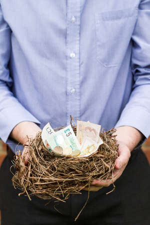 Man holding nest filled with Btitish money. This nest was an abandoned nest found in a hedge that was being removed.
