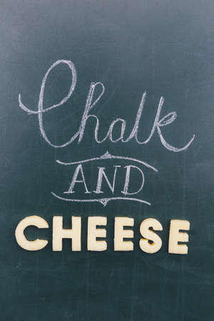 Chalk and Cheese saying written on chalkboard and letters cut from cheese Stock Photo