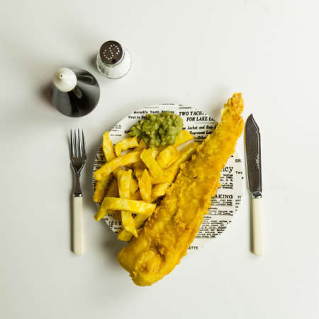 Traditional British takeaway meal of fish and chips with mushy peas on a newsprint plate Stock Photo
