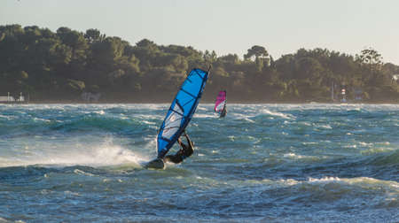 Windsurfing sliding on the Mediterranean, off Cannes, on a day of strong wind.