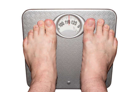 Weighing heavy man on the floor scales barefoot. Imagens