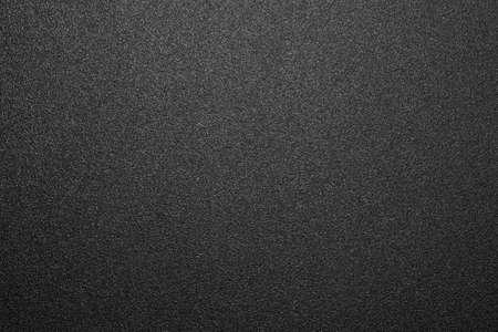 Textur aus schwarzem mattem Kunststoff. Mattschwarzer und weißer Hintergrund.