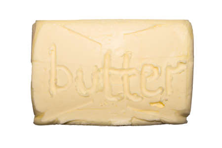 A piece of butter isolated on a white background. Reklamní fotografie