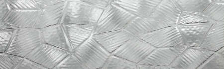 The glass is old, with a pattern.Texture of glass mosaic.Glass background with mosaic pattern. Foto de archivo