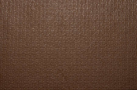 Texture of brown artificial leather with a pattern. The background is faux brown leather.