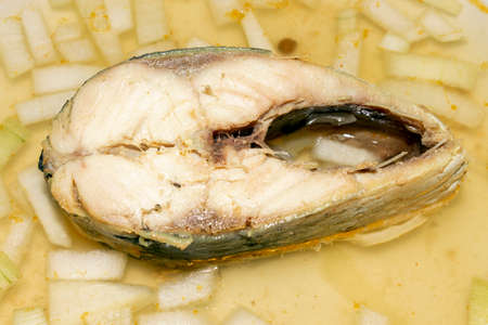Herring boiled in fish broth with onions.Fish soup.A piece of fish in fish broth with onions. Reklamní fotografie