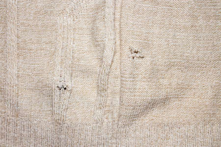 A hole in the knitted fabric. The background is a hole in the sweater.