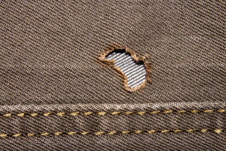 A hole in my jeans. Denim background with a hole. Hard-boiled denim.