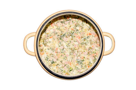 Olivier salad in a saucepan isolated on a white background. Olivier salad in a saucepan top view. 免版税图像