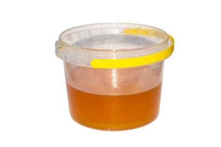 A jar of bee flower honey on a white background. Flower honey in a plastic bucket isolated.