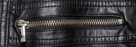 Black textured leather with metal zipper.Close-up of a black leather jacket with a zipper. 免版税图像