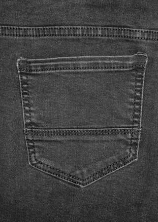 Texture dense denim fabric in black color. Background of black jeans. The background is black denim with pockets.