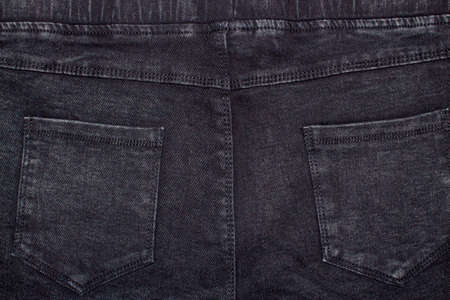 The texture of the dense denim fabric is dark blue. Blue jeans background. Background dark blue jeans with pockets.