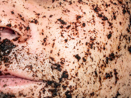Coffee Scrub For The Skin Of The Face.Natural coffee mask on a man's face.A man's dirty face.