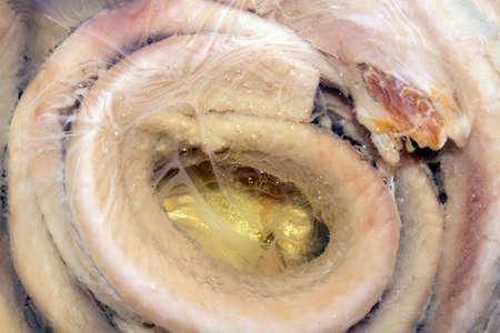 Fillet of salted herring in oil top view. Salted herring in oil background. Russian herring in oil.