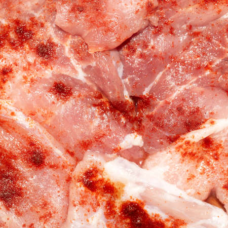 Thinly sliced raw meat in a marinade with red pepper.Raw meat in sliced background.Thin sliced meat for frying top view.
