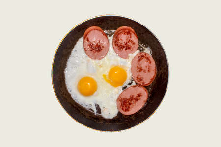 Fried chicken eggs with sausage in a frying pan top view. Homemade fried eggs with sausage in a frying pan on a white background.