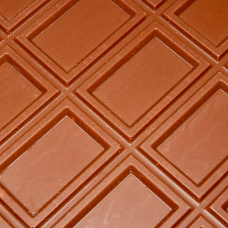 Milk chocolate is divided into blocks top view. Milk chocolate background with rectangular block pattern.