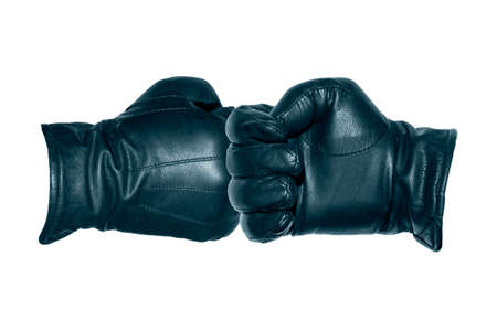 Two leather-gloved hands greet each other with a fist. Greeting each other with a gloved fist during a pandemic.