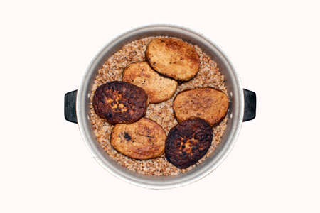 Meat cutlets with buckwheat in a saucepan on a white background. Buckwheat porridge with cutlets in a saucepan top view. Banco de Imagens