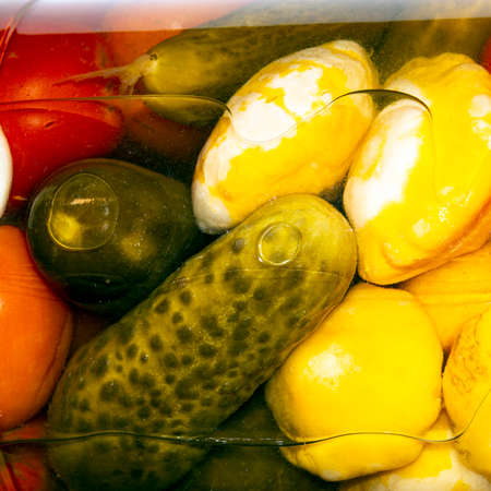 Pickled homemade cucumbers, tomatoes and squash. Pickled vegetables according to a home recipe background. Banco de Imagens