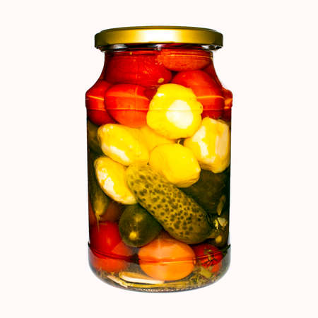 Pickled cucumbers, tomatoes and zucchini in a glass jar. Banco de Imagens