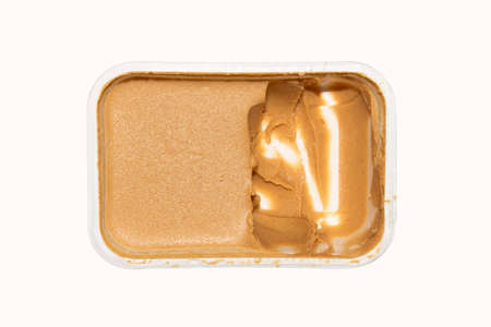 Peanut butter in a container on a white background top view.