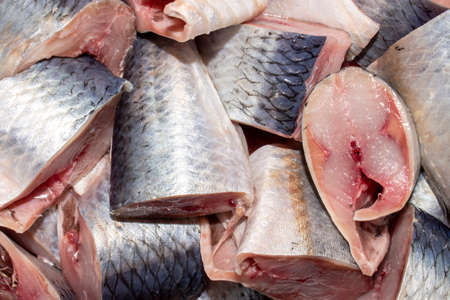 Salted herring cut into chunks.Background of pieces of pickled herring top view.