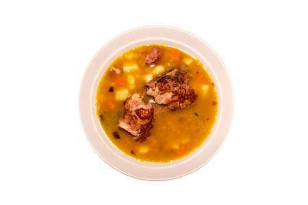 A plate of pea soup with smoked pork on a white background top view. 版權商用圖片