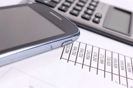Financial charts on the table with phone and calculator photo