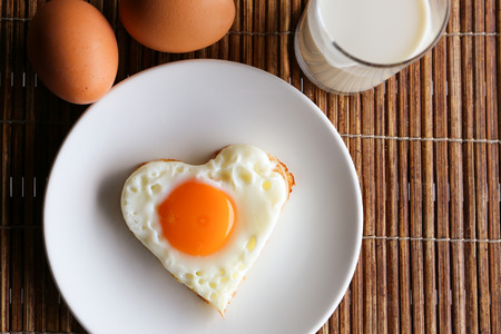 Fried egg in heart shape and milk