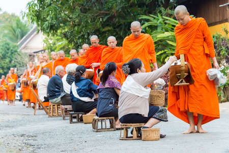 Luang Prabang, Laos - Mar 06 2015: Buddhist monks collecting alms in the morning. The tradition of giving alms to monks in Luang Prabang has been extended to tourists.