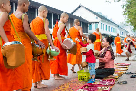 Luang Prabang, Laos - Mar 05 2015: Buddhist monks collecting alms in the morning. The tradition of giving alms to monks in Luang Prabang has been extended to tourists.