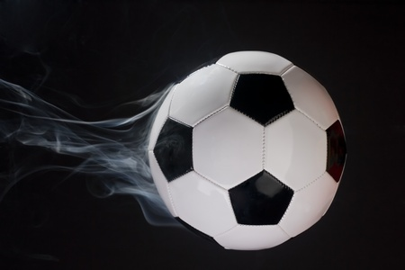 Smoking soccer ball illusion shot against a black background.