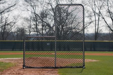 Pitching screen set on infield of baseball field