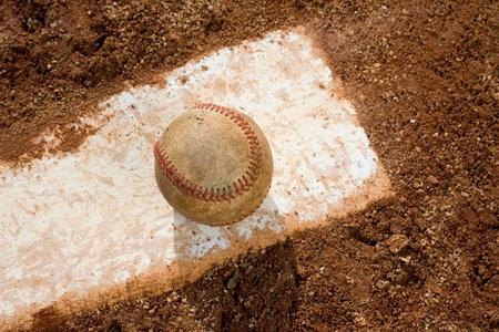 Old baseball on pitching rubber on baseball field photo
