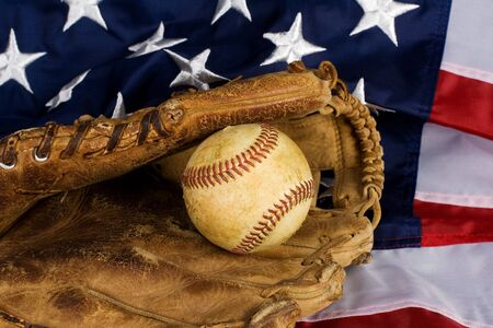 Old baseball in glove resting on American Flag