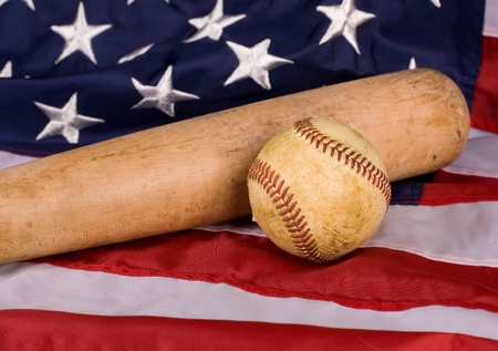 Old baseball and and bat with American flag. Focus is on ball.