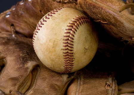 Worn baseball laying in an old glove Stock Photo - 9035390